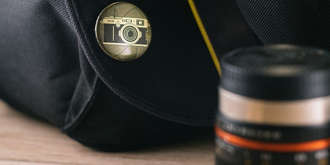 goldener Kamera Button an einer Kameratasche mit Objektiv
